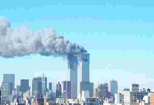 Towers aflame and smoking, against a blue sky